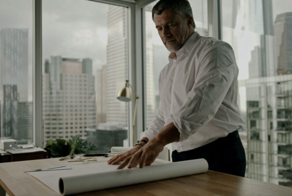Man unrolling paper on desk